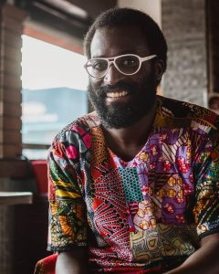 Mugabi Byenkya is a man of African decent with black skin. He wears white glasses, has a beard and wears a dashiki, which is a colorful garment for women and men from West Africa. Mugabi is smiling widely at the camera.