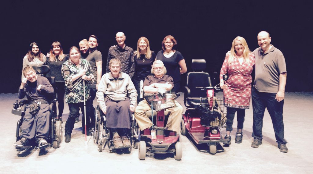 A group photo of thirteen participants of Wheel Voices Power Play. Some individuals use mobility devices.